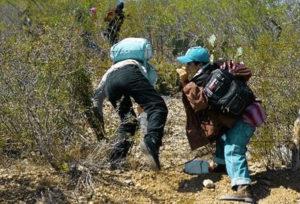 migranti attraversano filo spinato